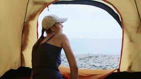 La donna aprire la zip la tenda dentro e gli sguardi in mare che allunga le sue armi nella mattina stock footage