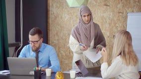 La donna araba e caucasica è discutente e prendente la carta nell'ufficio moderno stock footage