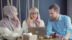 La donna araba e le paia caucasiche sono parlanti e guardanti sul computer portatile in caffè video d archivio