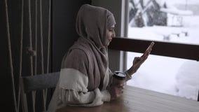 La donna araba sta guardando il video e l'immagine in smartphone che si siede in caffè stock footage
