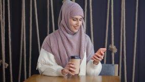 La donna araba sta scrivendo gli sms a macchina in smartphone, sedentesi in caffè con il cartone di caffè archivi video