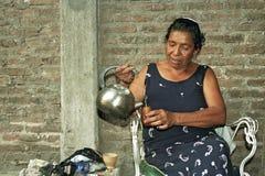 La donna argentina più anziana versa l'acqua per il tè del compagno immagine stock