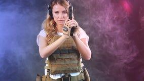 La donna in armatura protettiva tiene la pistola in mani Esercito, dedica, tecnologia Movimento lento archivi video