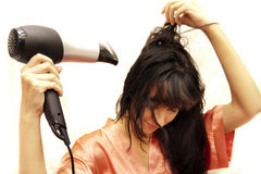 La donna asciuga i capelli l'asciugacapelli Fotografie Stock Libere da Diritti