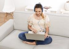 La donna ascolta musica sul suo computer portatile Immagine Stock