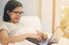 La donna asiatica è soddisfatta del computer portatile e dei ricevitori telefonici Immagini Stock Libere da Diritti