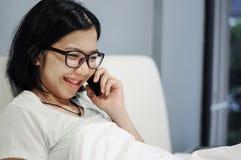 La donna asiatica è soddisfatta e sorriso del telefono cellulare su un letto Immagini Stock