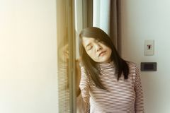 La donna asiatica è un'emicrania sul letto dopo sveglia di mattina, deprime la donna a casa, problema sanitario di malattie del c fotografia stock