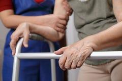 La donna asiatica anziana che usando un camminatore a casa con la figlia prende il Ca immagine stock libera da diritti
