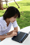 La donna asiatica attraente è all'aperto con il computer portatile Immagini Stock