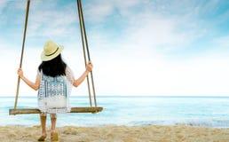 La donna asiatica in cappello di usura di stile casuale ed i sandali si siedono sulle oscillazioni alla spiaggia di sabbia ed a s immagine stock libera da diritti