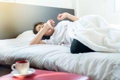 La donna asiatica che allunga e che sbadiglia sul letto dopo sveglia di mattina Immagini Stock