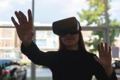 La donna asiatica che indossa l'attimo della macchina fotografica di VR gode di di giocare fotografie stock