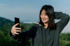 La donna asiatica che porta un rivestimento dell'inverno, prende un telefono del selfie, prende le immagini nella zona turistica  fotografia stock libera da diritti