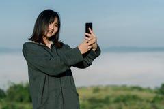 La donna asiatica che porta un rivestimento dell'inverno, prende un telefono del selfie, prende le immagini nella zona turistica  immagine stock libera da diritti