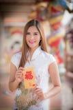 La donna asiatica in cinese veste il distico della tenuta 'felice' (Chine fotografia stock libera da diritti