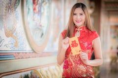La donna asiatica in cinese veste il distico della tenuta 'felice' (cinese w fotografie stock