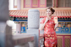 La donna asiatica in cinese veste il distico della tenuta 'lucrativo' (C Fotografia Stock Libera da Diritti