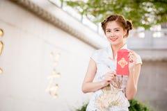 La donna asiatica in cinese veste il distico della tenuta 'lucrativo' (C Immagine Stock