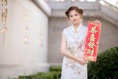 La donna asiatica in cinese veste il distico della tenuta 'lucrativo' (C Immagini Stock Libere da Diritti