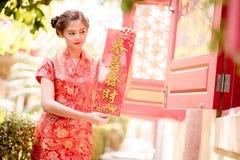 La donna asiatica in cinese veste il distico della tenuta 'lucrativo' (C Fotografia Stock
