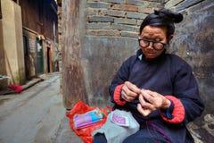 La donna asiatica con i vetri è impegnata in cucito all'aperto, Chin Fotografia Stock Libera da Diritti