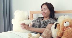 La donna asiatica con l'orsacchiotto riguarda il letto stock footage
