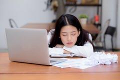 La donna asiatica con sovraccarico stanco e sonno, ragazza ha riposo mentre nota di scrittura del lavoro, Fotografia Stock Libera da Diritti