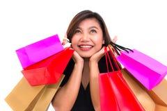 La donna asiatica con variopinto porta i sacchetti della spesa in sue mani sorride e felicità Occhiali da sole Fotografie Stock Libere da Diritti