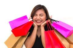La donna asiatica con variopinto porta i sacchetti della spesa in sue mani sorride e felicità Occhiali da sole Fotografia Stock Libera da Diritti