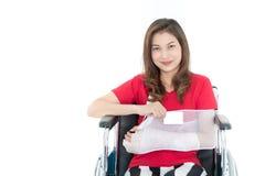 La donna asiatica del braccio rotto con l'imbracatura del braccio patrocinata in sue mani si siede immagine stock libera da diritti