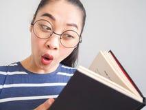 La donna asiatica del nerd ha ottenuto un'idea sorpresa dal libro Immagini Stock Libere da Diritti