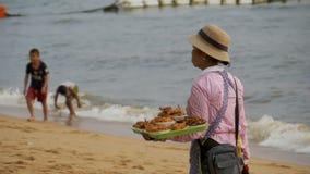 La donna asiatica del venditore porta le vendite tropicali dell'alimento sulla spiaggia Pattaya, Tailandia stock footage