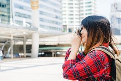 La donna asiatica del viaggiatore bello felice porta lo zaino Le giovani donne asiatiche allegre che usando la macchina fotografi Fotografia Stock