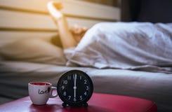 La donna asiatica della sfuocatura sveglia l'allungamento e sbadiglia sulla camera da letto con l'orologio nero del ` della svegl Fotografia Stock