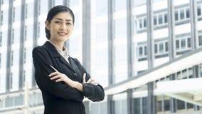 La donna asiatica di affari sta con l'invio sicuro ad all'aperto fotografia stock libera da diritti