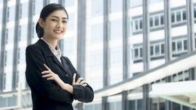 La donna asiatica di affari sta con l'invio sicuro all'unità di elaborazione all'aperto fotografia stock
