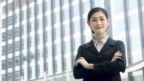 La donna asiatica di affari sta con l'invio sicuro all'unità di elaborazione all'aperto immagine stock