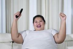 La donna asiatica di peso eccessivo felice ha serrato i suoi pugni mentre teneva un telecomando fotografia stock libera da diritti
