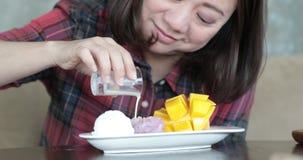 La donna asiatica felice versa il latte di cocco sul mango e sul riso appiccicoso archivi video