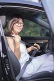 La donna asiatica fissa la cinghia della sede di automobile prima prende un azionamento Fotografia Stock