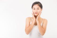 La donna asiatica massaggia il suo fronte ed applica il cosmetico crema Fotografia Stock Libera da Diritti