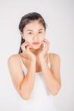 La donna asiatica massaggia il suo fronte ed applica il cosmetico crema Immagine Stock Libera da Diritti