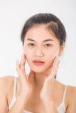 La donna asiatica massaggia il suo fronte ed applica il cosmetico crema Fotografia Stock