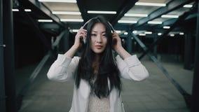 La donna asiatica mette sopra la cuffia che cammina alla metropolitana di notte video d archivio