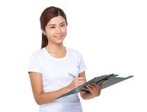 La donna asiatica prende nota sulla lavagna per appunti Fotografie Stock