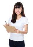 La donna asiatica prende nota sulla lavagna per appunti Fotografia Stock