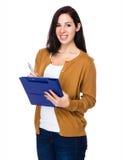 La donna asiatica prende nota sulla lavagna per appunti immagine stock