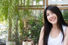 La donna asiatica si siede al caffè all'aperto giovane adulto femminile con naturale Fotografia Stock Libera da Diritti