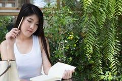 La donna asiatica si siede al caffè all'aperto giovane adulto femminile con naturale Immagini Stock Libere da Diritti
